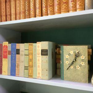 En bok som är omgjord till en klocka och en låda som det limmats bokryggar på.