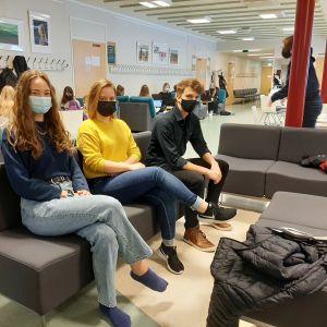 Tre studerande sitter på soffa.