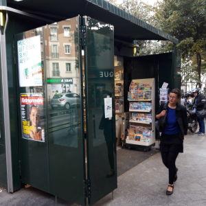 En person går förbi en tidningskiosk i Frankrike.