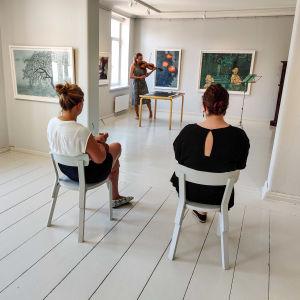 Två kvinnor sitter på varsin stol inne i ett vitmålat rum och ser på en kvinna som spelar violin.