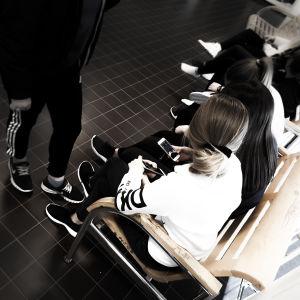 Ett gäng unga sitter på en stolrad. Kontrasterna på bilden är starka.