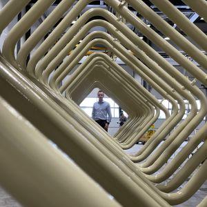 Toimitusjohtaja Tommi Lähteinen seisoo kuivumassa olevien maalattujen metalliosien takana.