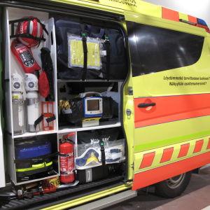 Ambulansens utrustning syns genom bilens öppna dörr.