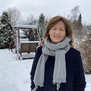 En kvinna i en snöig trädgård.