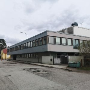 En stor vit byggnad vid en asfalterad gata.