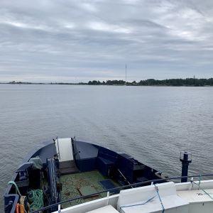 Fotot är taget på ett fartyg, på väg mot Mjölö. En del av den blåa fören på båten syns, och i bakgrunden ser man klippor som tillhör Mjölö. Det är annars mulet och grått.