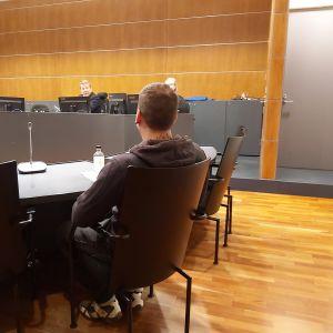 En ung man sitter på en stol i en rättssal, ryggen mot betraktaren. Han står åtalad för grovt skattebegrägeri i vad som är Finlands första Onecoin-rättegång.