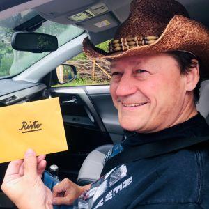 Stetsonpäinen mies istuu autossa ja näyttää kameralle hymyillen kirjekuorta