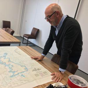 Ordföranden för det holländska fiskarförbundet böjer sig över en karta över Storbritannien i sitt arbetsrum.