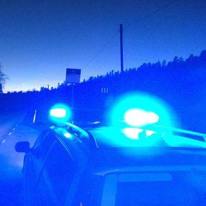 Bil med blåljus kör i mörker på landsväg.