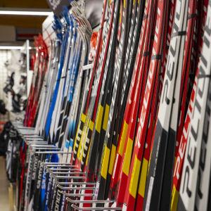 Nya färggranna skidor på rad i en hylla i en sportaffär.