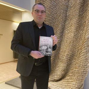 Jussi Niinistö seisoo kirja kädessään.