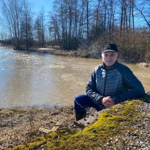 En äldre man sitter invid kanten av en å. I bakgrunden syns träd och en åker.