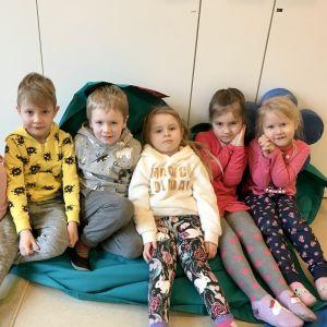 Sex dagisbarn sitter på en stor blå kudde.
