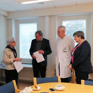 En man och en kvinna överräcker ett papper till tre personer, två män och en kvinna. Den ena mottagande mannen i vit läkarrock.