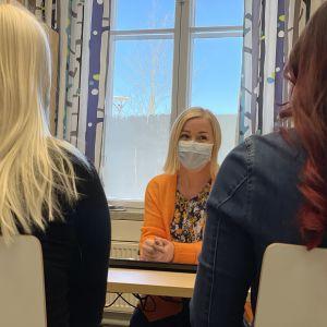 Pauliina Pöntinen juttelee kahden opiskelijan kanssa työhuoneessaan.