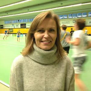 Lena Törnqvist står inne i Aurorahallen med innebandyspelare i bakgrunden.