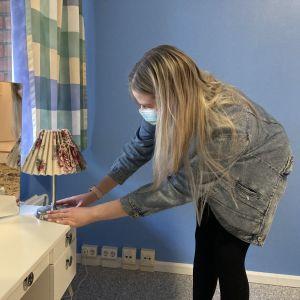 Tyttö asettelee lamppua meikkipöydälle.