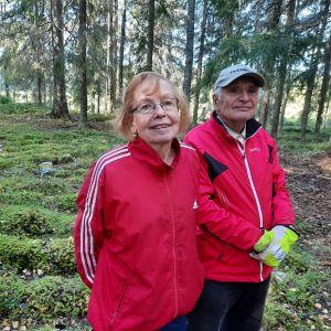 ett äldre par står intill en stenlabyrint i en skogsglänta