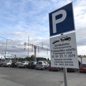 Siirtokehotusta osoittava kyltti Kokkolan rautatieaseman parkkipaikalla.