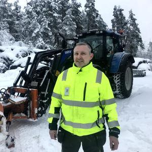 Man i arbetskläder framför traktor med snöplog.