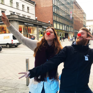 Milli Hellström och Christoffer Kaski iförda röda näsor framför en gata med människor som går.