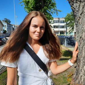 En kvinna står ute i en park intill ett träd