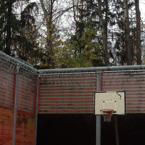 Gården på Krämertsskogs förvarsenhet är omringad av taggtråd och höga murar
