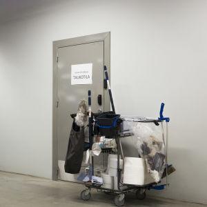 Siivousvälinekärry oven edessä.