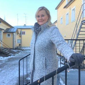 Helena Hemming står på en trappa och tittar in i kameran.