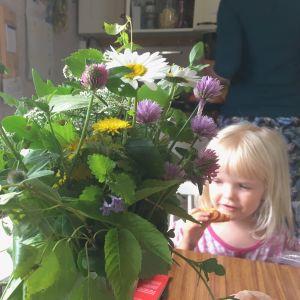 Ines Holmström äter bulle bakom en bukett med ätbara växter.