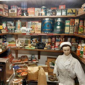 litet butikmuseum med docka föreställande ett butiksbiträde omgivet av butiksinredning och förpackningar