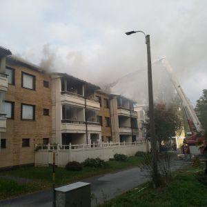 Rök stiger upp ur takkonstruktionerna på ett tegelhus.