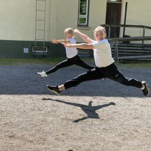 Två flickor hoppar med utsträckta ben.