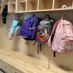 Fyra färggranna skolväskor hänger på en vägg med klädhängare på ett daghem.