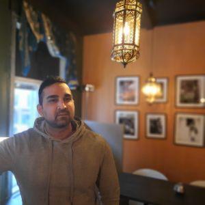 En man står i en indisk restaurang med österländsk inredning.