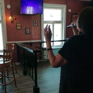 Nainen laulaa karaokea