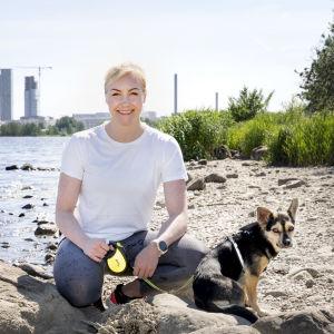Emma Kimiläinen rannalla koiransa kanssa.