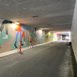 Kajaanin Prisman alikulkutunneli tarjoaa parisataa metriä maalattavaa alustaa taiteilijoille. Taka-alalla taiteilija Laura Lehtinen maalaa niittyleinikkiä seinään.