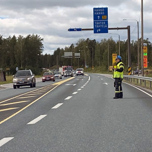 Person dirigerar trafiken på väg 51 vid avtaget till Täkter.