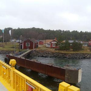 Utsikten mot röda trähus på stranden i Kittuis från landsvägsfärjan som anländer till Houtskär.
