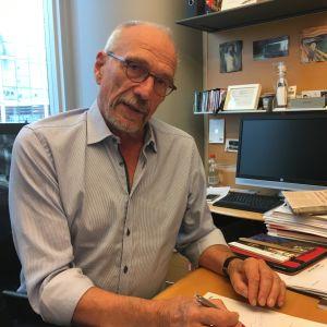 Nils Torvalds sitter vid ett skirvbord.