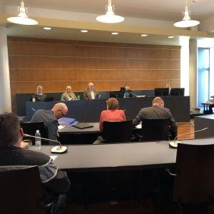 Bild från rättssal med flera personer i bild, endast ryggtavlan kan ses på dem som sitter närmast.