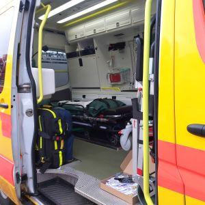 Ambulans med öppen sidodörr.
