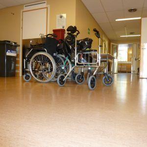 Rullstol och rollator i en sjukhuskorridor.