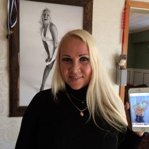Kvinna håller i telefon där en erotisk målad bild av henne visas