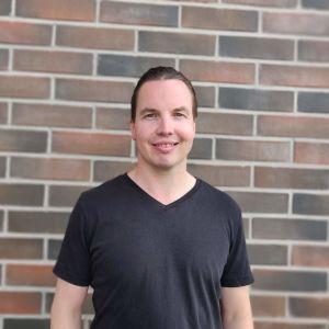 Janne Raninen står framför en tegelvägg i svart t-skjorta.