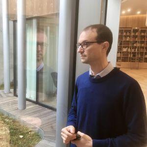 Michael Pärt tittar ut genom ett fönster mot en av Arvo Pärt-centrets små innergårdar.