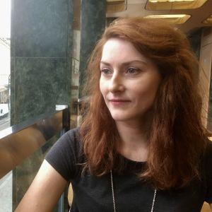 Kateřina Cidlinská tittar ut genom fönstret mot gatan i Prag.