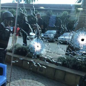 En beväpnad soldat tar skydd invid ett fönster som genomborrats av kulor.